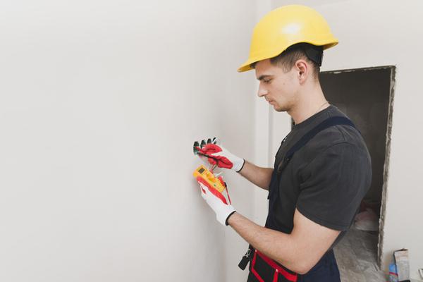 homem arrumando eletricidade na parede